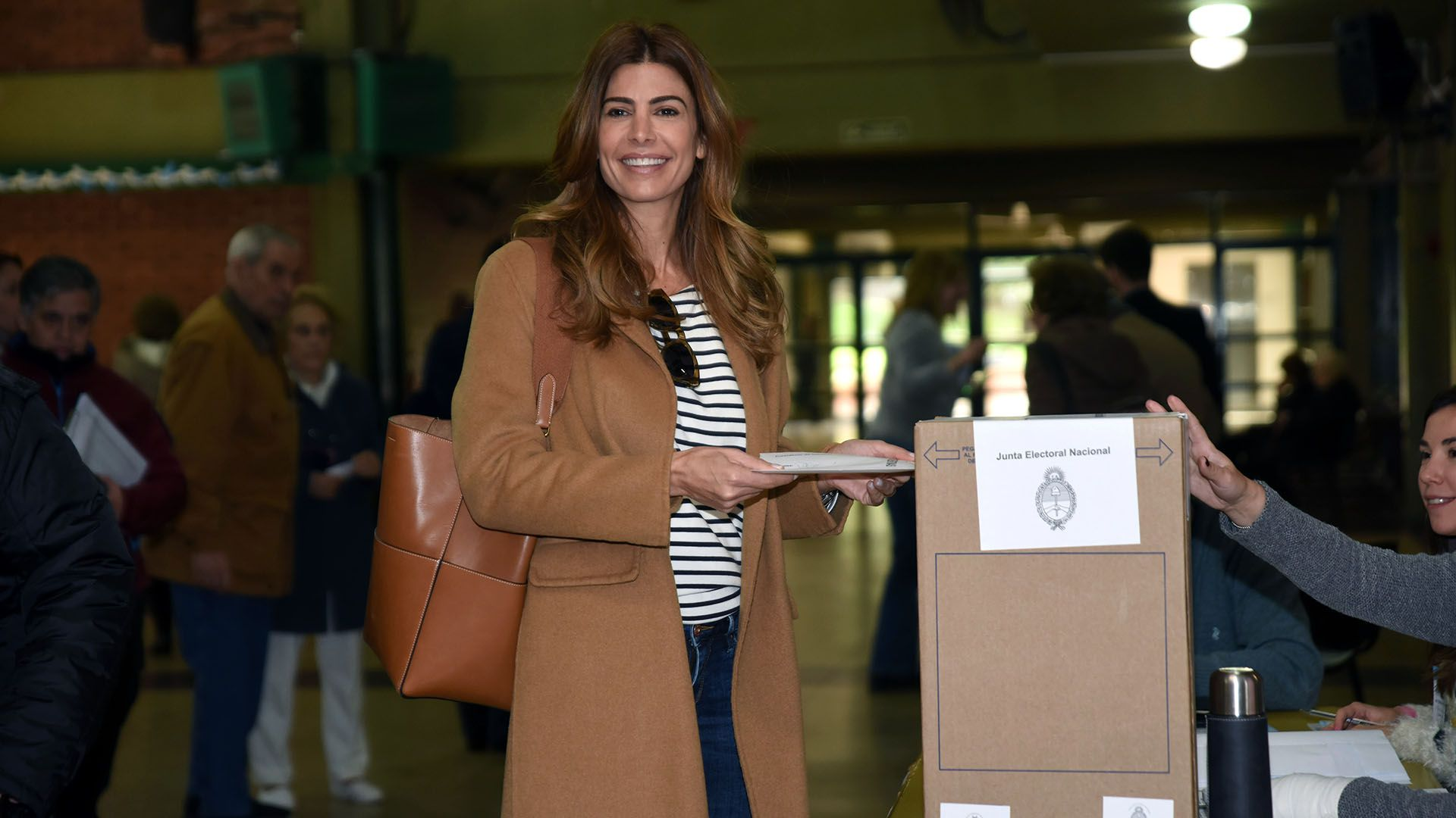 Juliana Awada votando con su maxi tapado color camel, remera rayada y jeans recto (Franco Fafasuli)