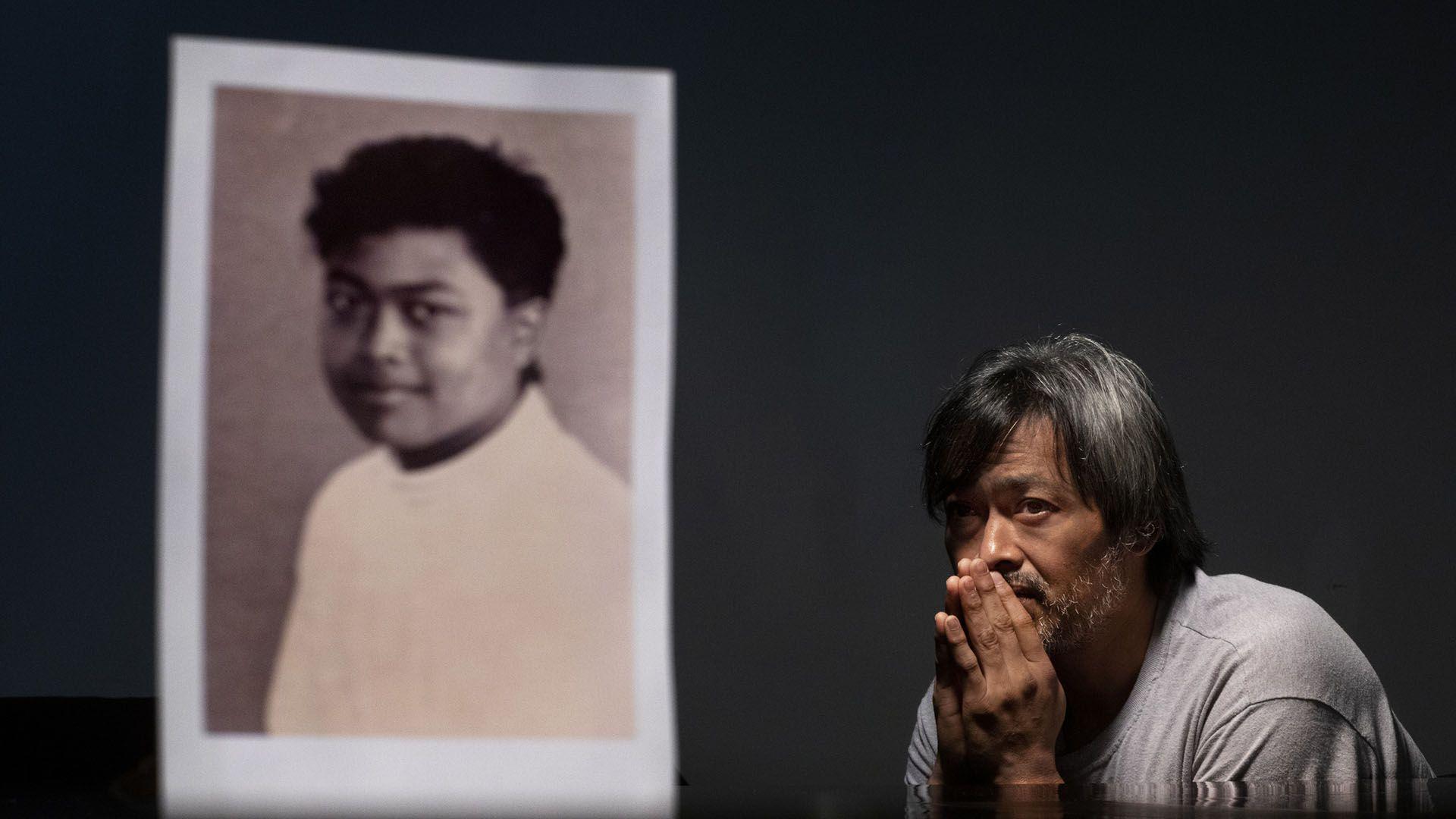 Mark Apuron, 45,junto a su foto de cuando fue abusado por el ex arzobispoAnthony Apuron (AP Photo/David Goldman)