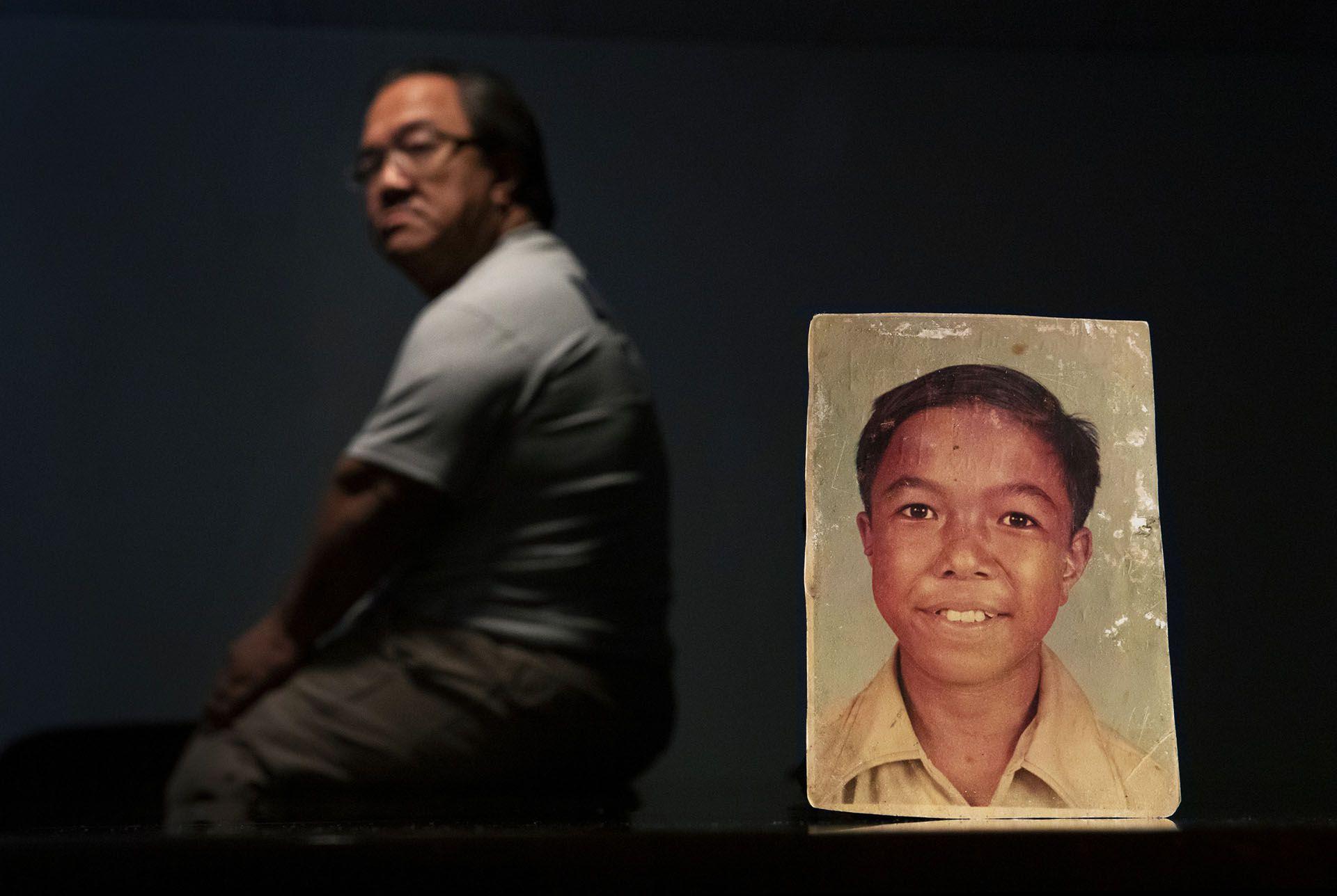 Una víctima de abuso sexual identificado con las iniciales C.M.V., 58,junto a una foto suya de cuando era niño, enGuam (AP Photo/David Goldman)